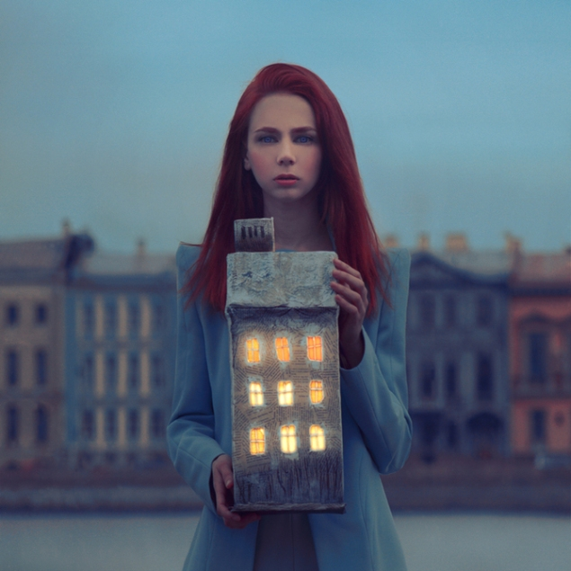Girl holding a model house